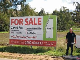 Mark Burns puts up the for sale sign on the land in Macartney Street.