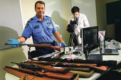 Police media officer Joshua Marshall-Clarke films Armadale officer-in-charge Senior Sergeant John Bouwman with some of the items seized or recovered during the operation. Picture: Marcelo Palacios d405812
