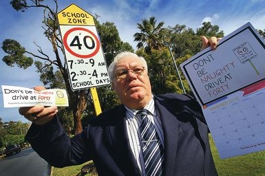 Councillor Terry Brown with a new 'Don't be naughty – drive at forty' sticker promoting the speed limit for school zones on school days. Picture: Marcelo Palacios www.communitypix.com.au d404958