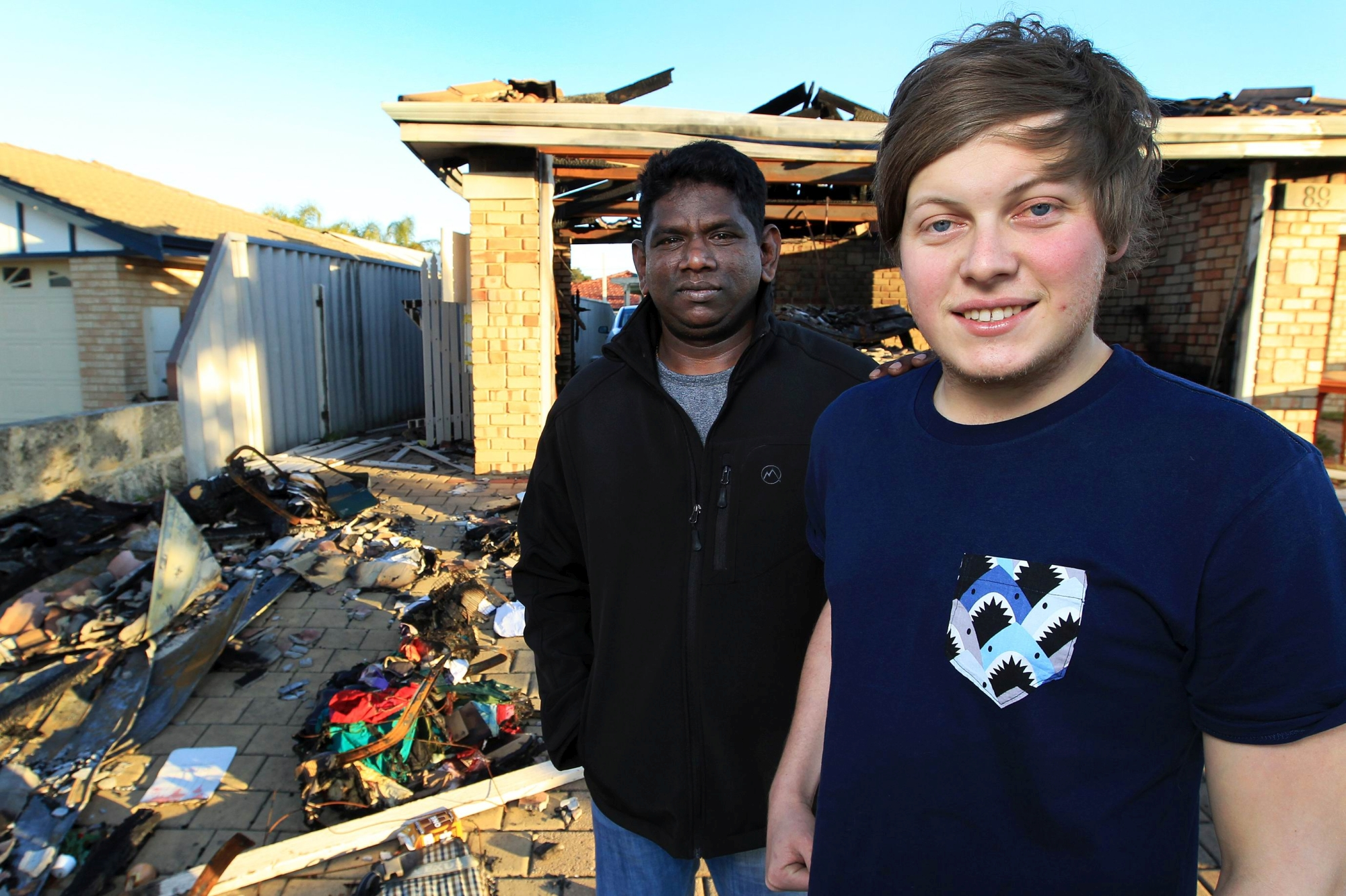Kanaga Sinnasamy (left) with Joel Lipple in the front yard of the gutted house. Picture: Marcelo Palacios d404636