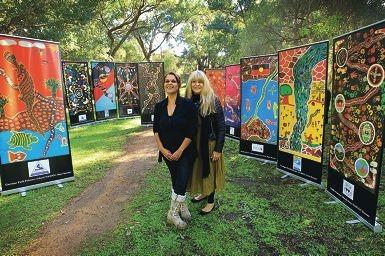 "Alta Winmar and Tjalaminu ""TJ"" Mia with the strikingly colourful Naidoc banners."