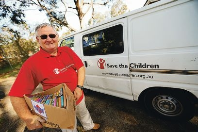 Volunteer driver Allen Taylor with a box of books donated for the 49th annual Save the Children Book Sale.
