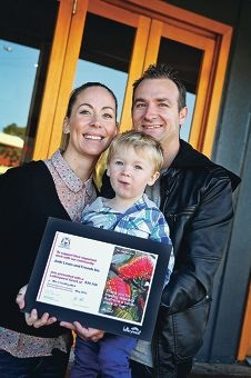 Jade and Tristan Lewis with their son Noah (2) and the Lotterywest grant memento.