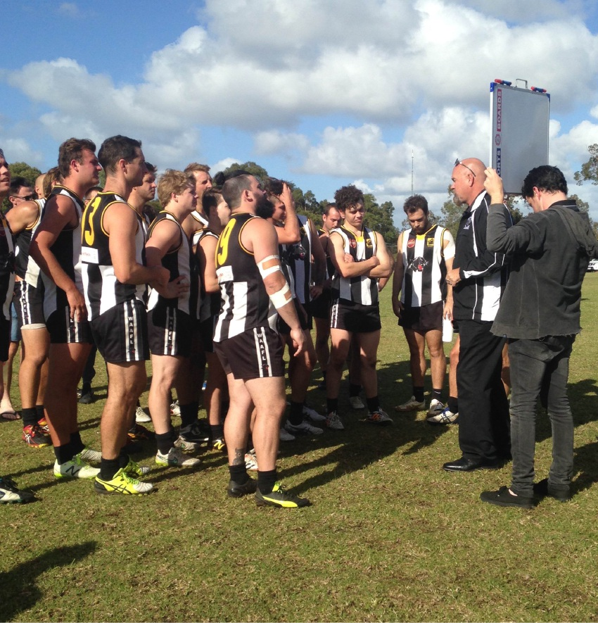 Reserves coach Russell Banks addresses his team.