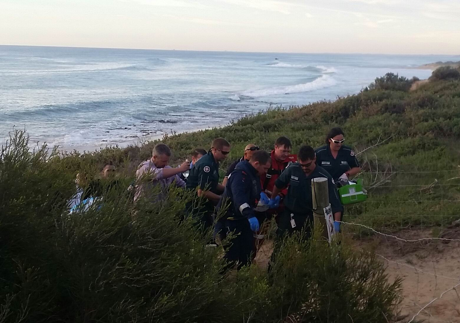 The man is carried up the beach to the waiting ambulance.