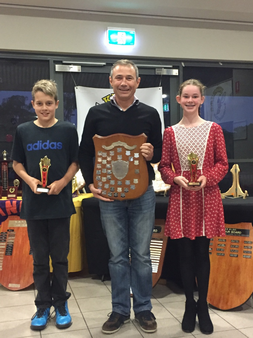 Zachariah Morrissey and Kirra Russell receive the Doug Mickle Shield 11-13yr Intermediate Champions awards from Roger Cook.