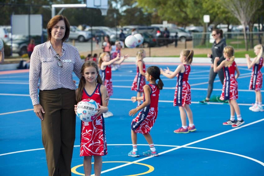 Members of the Doves netball team put the new netball court to the test, watched by St Stephen's School head of primary Darnelle Pretorius and student Ireland George.