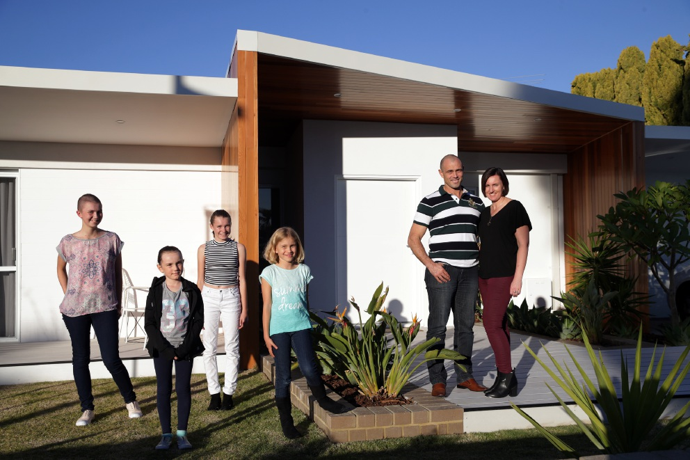 First: Ryan and Sallie HoyPoy with children Zoe (15), Imogen (7), Brianna (13) and Lacey (9) in front of their renovated home. Second: Cricket legend Adam Gilchrist with Matt and Kim. Then: Volunteers at work on the home. Pictures: Martin Kennealey        www.communitypix.com.au   d450824