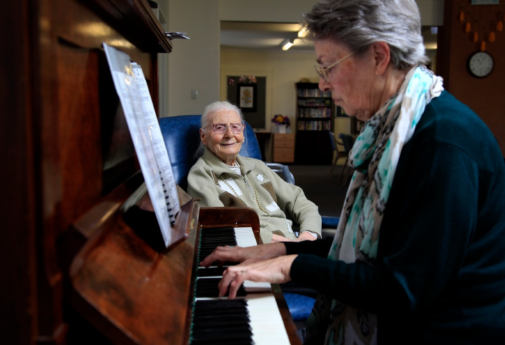 Rossmoyne Waters resident Denise Theobald (94) listening to Wendy Millen (Village resident) playing the piano. Picture: Marie Nirme d453929