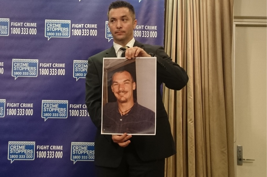 Detective Sergeant Lampard with a photo of Alan Taylor.