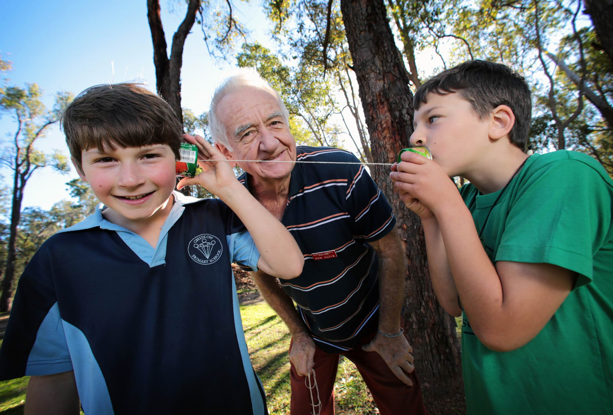 L-R: Cody O'Brien (10) of Chidlow, Ron Klein from the Mundaring Men's Shed and Zayne Campbell (9) of Chidlow, playing with old style toys made by the Mundaring Men's shed, which includes a tin can telephone.  Earth Day fun at Chidlow Primary School.