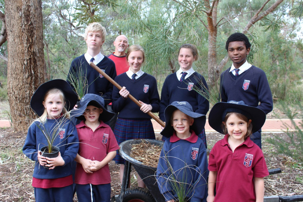 Foundation Christian College groundsman Mark Stewart with students planting grass trees.