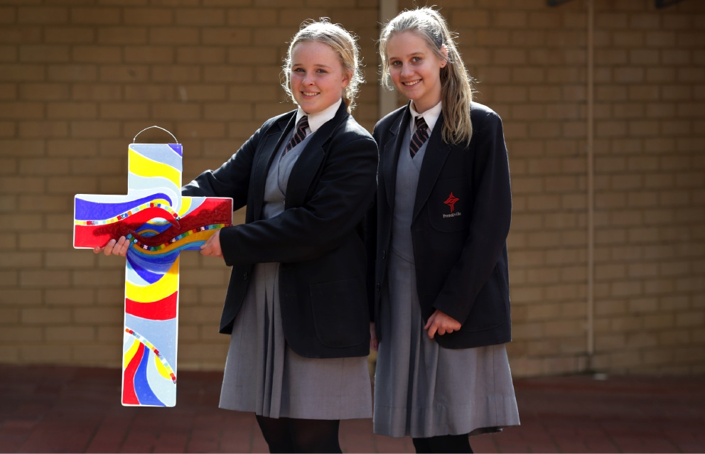 Year 8 students Jordyn Fahie and Madison Snelling with a glass cross.  Picture: Martin Kennealey        d455544