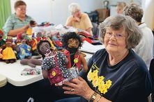 Group member Joyce Brockway helps with the doll project.