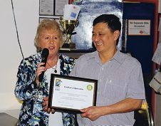 Jacquie Harry hands John Tran a certificate of appreciation.