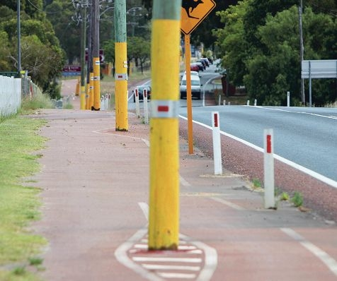 The cycle path on West Swan Road splits in two around poles, painted in bright yellow safety colours.