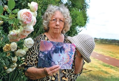 Jean Cooper with a picture of her dead cat and the hat one of the women left behind. Picture: Matt Jelonek d429135