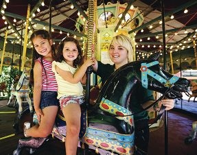 Grace and Georgia Scolt, of Success, with carousel operator Alissa Harper. Picture: David Baylis www.communitypix.com.au d427952