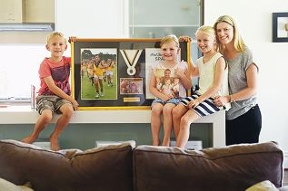 Tash Spanjich with her children Jeremy (6), Chloe (4) and Mia (9) and a framed Swan Athletic Football Club photograph celebrating the life of husband and father Paul |Spanjich. Picture: Marcus Whissonwww.communitypix.com.au d428104