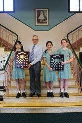 Santa's Junior Piano Trio members Celine Ng, Gwyneth Chua and Kate Naunton-Morgan present their trophies with principal Ian Elder.