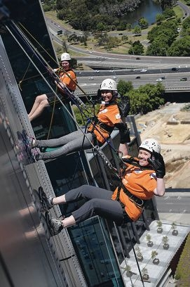 Fiona Elmer, Kim Dupuy and Daniel Loden abseiling down the Woodside building for PMH.