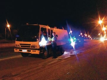 A police officer speaks to the driver of the street sweeper on the Mitchell Freeway on Tuesday night.