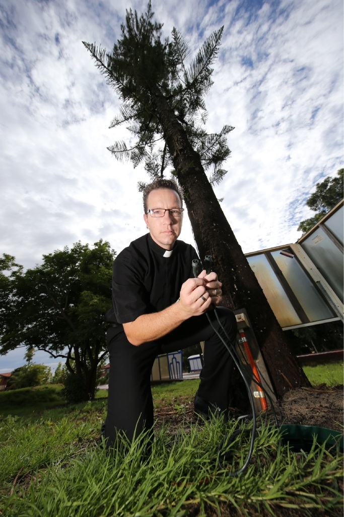 Father Stephen Conway in front of the Christmas lights display, which was damaged by vandals last week.  Picture: Andrew Ritchie         www.communitypix.com.au   d448190