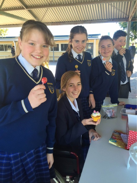 Josephine Byrne, in a wheelchair, with students at her cupcake fundraising stall.