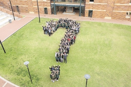 Students celebrate their new science building by forming the symbol for curious minds.