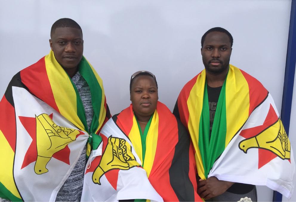 Keith Makuni, Lucky Ngoshi and Marshal Mtangwani wearing the Zimbabwean flag.