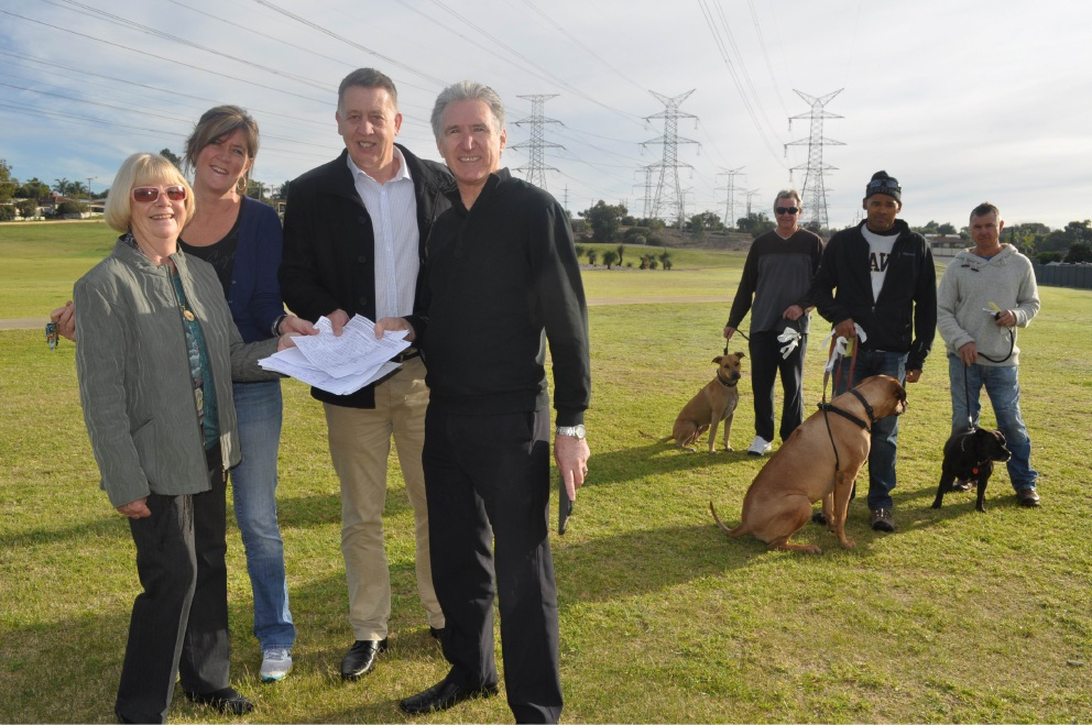 Aileen Hamill, Dee Walton-Bence, councillors Phil Eva and Steve Portelli, Luke Hills with dog Stella, Lowell Ellis with dog Rafiki, and Sean Bence with Daisy at the parcel of land they hope can become a dog exercise area.