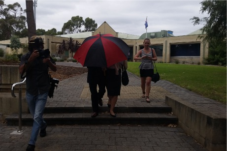 The accused teacher leaves the Mandurah Magistrates Court under cover of an umbrella. Picture: Rachel Fenner.