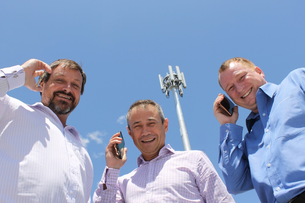 Telstra area general manager Guy Champion, local member Roger Cook and Trevor Gross from the Public Transport Authority test the new service.