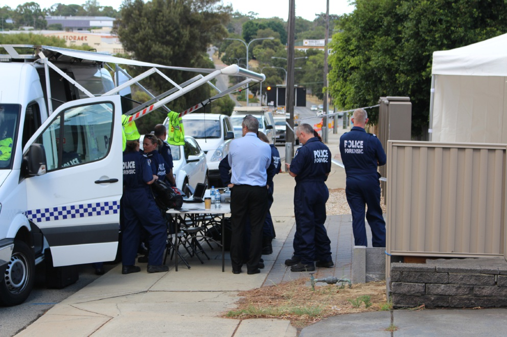 Forensic officers gather outside the Leach Highway home of a deceased Melville woman early Friday morning.
