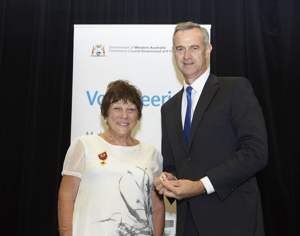 Meg Loveland receives her badge from Minister Tony Simpson.