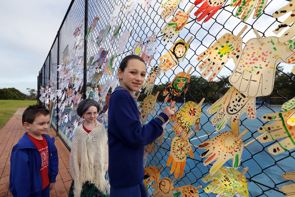 Locrin,Lavanna and Scarlett Gosper at the fence where the paper hands were displayed. Picture: Martin Kennealey www.communitypix.com.au   d457195