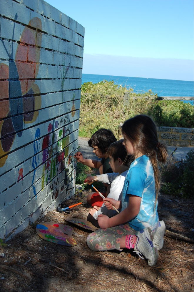 Children painted a mural on a brick wall ahead of the garden workshop.