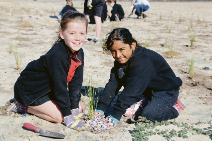 Edney Primary School students Victoria Outten and Lalita Puvanendran plant seedlings at Perth Airport last week
