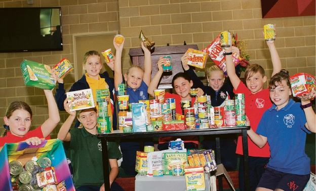 Dixie Williams, Amber Nagel (seated), Mikaylah Pfeiffer, Rylee Hancock, Charlotte Adams, Reese Hancock, Angus Shore, Shianne Peck with some of the food they have donated to the St George's Cathedral food drive. Picture: Robin Kornet. d454702
