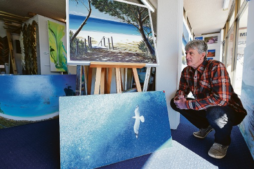 Summers Gallery owner David Woodley with two of Mark Waller's paintings.