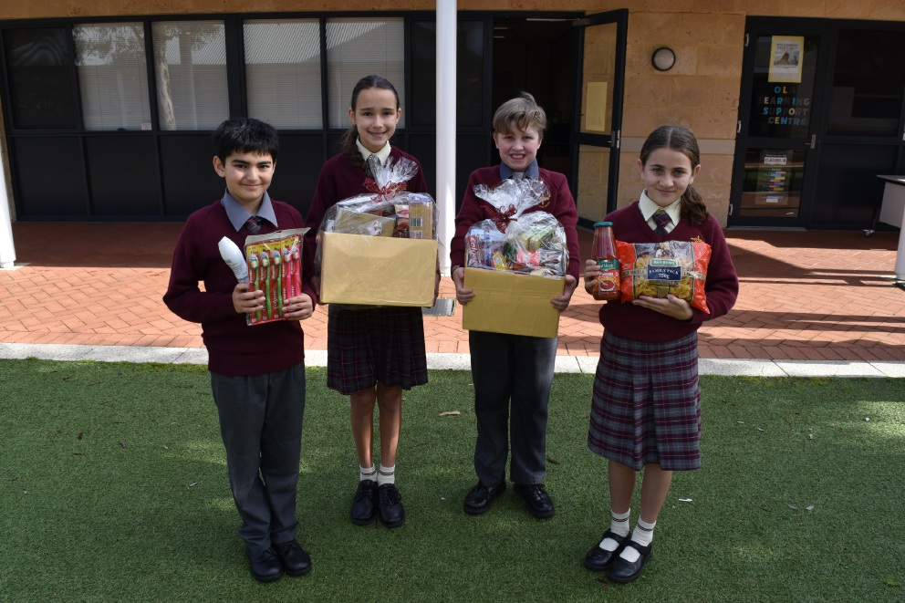 Mackenzie Jubb, Taine Knight, Ermillie Lomma and Laura Ammendolea hold boxes full of winter items for homeless people.