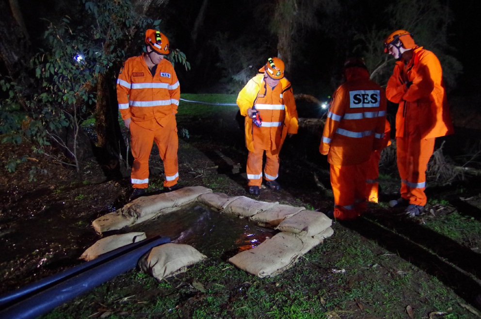 SES volunteers use sandbags and plastic sheeting to divert stormwater.