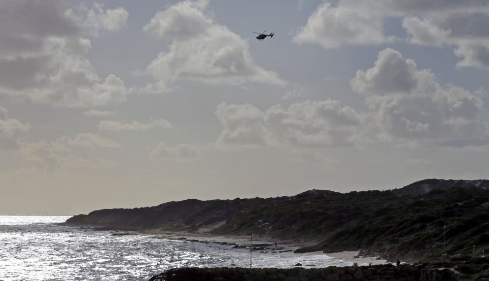 A helicopter searches the Burns Beach coast for missing man Daniel McCartney. Picture: Martin Kennealey
