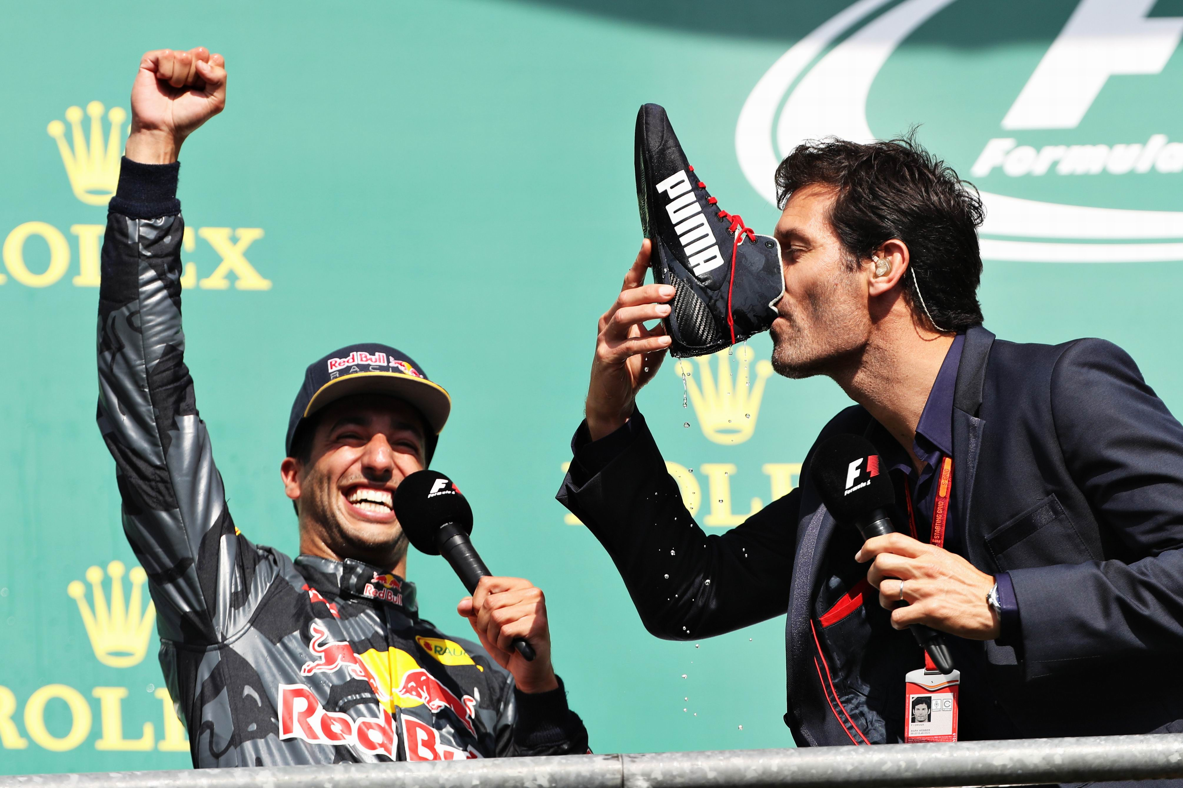 Mark Webber drinks champagne from the boot of Daniel Ricciardo. Picture: Mark Thompson/Getty Images