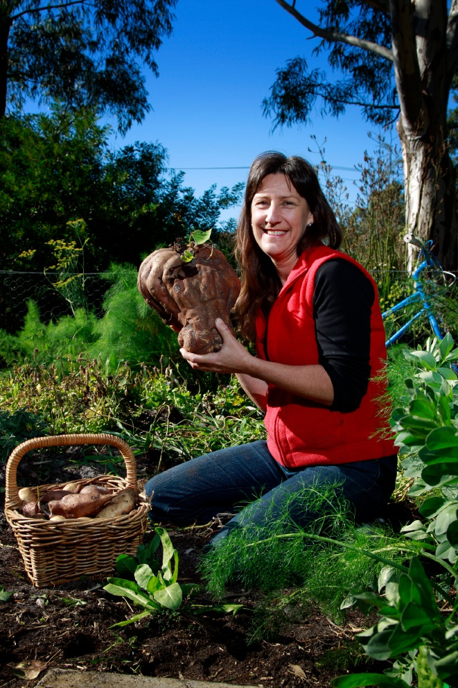 Faye Arcaro in her vegie garden with a giant sweet potato, which weighs about 7 kg. Picture: Marie Nirme
