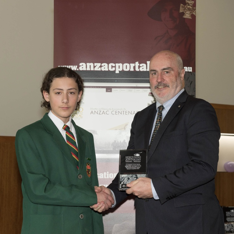 Csanad Horvath receives a plaque from |Department of Veteran Affairs' Simon Lewis.