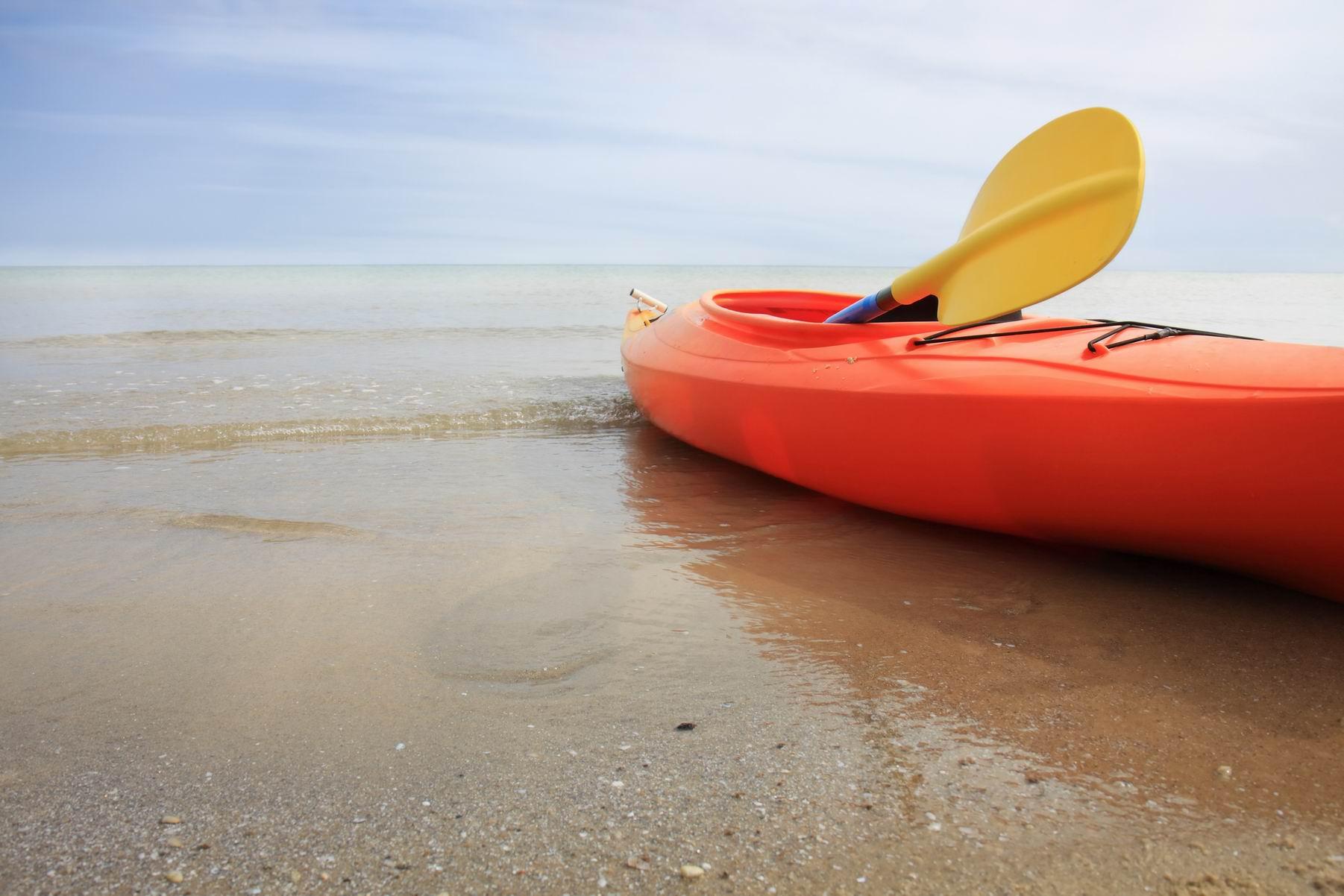 A bright orange kayak at the beach.
