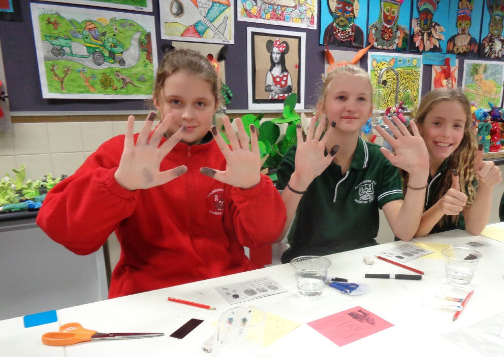 Year 6 students Emily Mottram, Sophie Eden and Darcy O'Connor experiment with the science of fingerprinting.