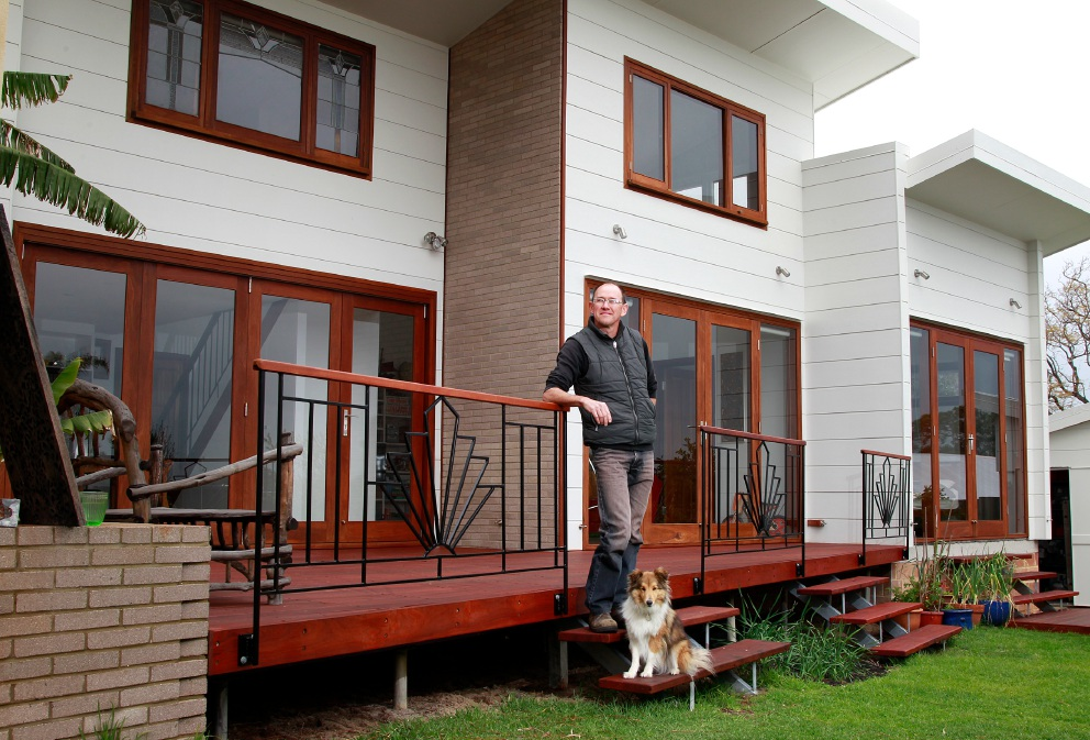 Guy Cameron pictured outside his solar passive home in Bicton with his dog Kenzie. Picture: Marie Nirme