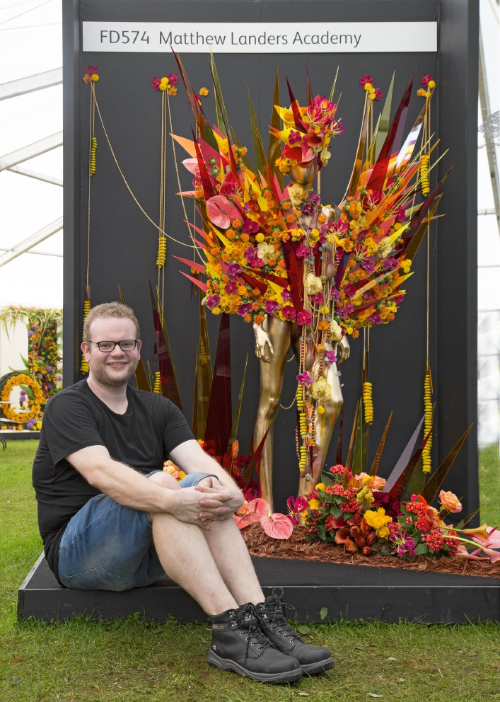Matthew Landers sits alongside his Rio Carnival costume display, a Royal Horticultural Society 2016 silver award-winner.